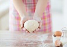 Slutet av kvinnlign räcker upp hållande bröddeg Arkivbild