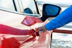 Slutet av kvinnor räcker upp öppningsdörren av bilen Royaltyfria Bilder
