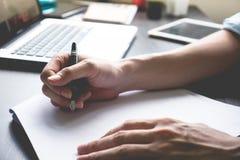 Slutet av mannen räcker upp handstil på papper på hans kontorsskrivbord Arkivbilder