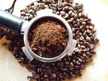 Slutet av metallportafilter fyllde upp med kaffepulver och kaffebönor omkring på trätabellen royaltyfria foton