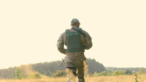 Slutet av militärens skuldra med roboten går upp i stäppen långsamt stock video