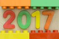 Slutet av 2017 plana plast-nummer med den plast- leksaken blockerar upp att inrama på träbakgrund Royaltyfri Bild