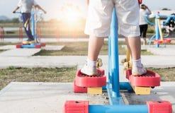 Slutet av pojkefot i gymnastikskor står upp på övningsmaskiner royaltyfria bilder