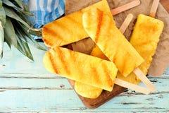 Slutet av sötsaken grillade upp ananaskilar mot blått trä Royaltyfri Fotografi