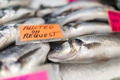 Slutet av spridning för havsbasen över is på monger's för en fisk marknadsför upp arkivbilder