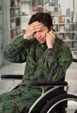 Slutet av stiligt barn för ett bekymmer tjäna som soldat upp sammanträde på hjulstol som använder hans mobiltelefon, i en suddig  Arkivfoton