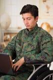 Slutet av stiligt barn tjäna som soldat upp sammanträde på hjulstol som använder hans dator över hans ben som bär den militära li Royaltyfri Bild