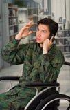 Slutet av stiligt barn tjäna som soldat upp sammanträde på hjulstol som använder hans mobiltelefon som bär den militära likformig Royaltyfri Bild