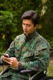 Slutet av stiligt barn tjäna som soldat upp sammanträde på hjulstol som använder hans mobiltelefon i det fria, i en trädgårdbakgr Arkivbilder