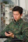 Slutet av stiligt barn tjäna som soldat upp sammanträde på hjulstol som använder hans mobiltelefon, i en suddig bakgrund Fotografering för Bildbyråer