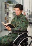 Slutet av stiligt barn tjäna som soldat upp sammanträde på hjulstol som hemma läser en bok, i en suddig bakgrund Arkivbilder