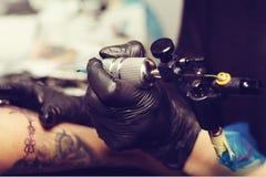 Slutet av tatueringkonstnären räcker upp att skapa en tatuering på en arm för flicka` s royaltyfri fotografi