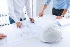 Slutet av teknikern räcker upp att diskutera ett byggnadskonstruktionsprojekt på arbetsplatsen arkivbilder