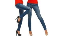 Slutet av två kvinnor lägger benen på ryggen upp i jeans royaltyfri foto