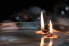 Slutet av två sväva stearinljus i mutter beskjuter upp - jultema Royaltyfri Fotografi