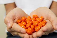 Slutet av ungen räcker upp att rymma många vitaminpreventivpillerar arkivfoton