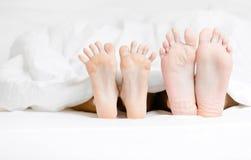 Slutet beskådar upp av fot av koppla ihop som ligger i säng Royaltyfri Bild