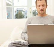 Slutet beskådar upp av yrkesmässig man med bärbar dator, och smart ringa hemma. Royaltyfria Foton