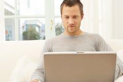Slutet beskådar upp av yrkesmässig man med bärbar dator, och smart ringa hemma. Royaltyfri Fotografi