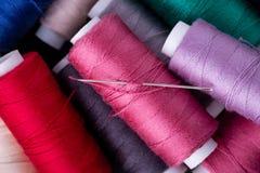 Slutet för bästa sikt av den spridda färgrika bomullstråden rullar ihop upp med visaren arkivfoto