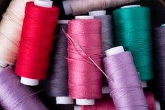 Slutet för bästa sikt av den spridda färgrika bomullstråden rullar ihop upp med visaren royaltyfri foto