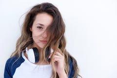 Slutet kyler upp den unga kvinnan med head telefoner mot vit bakgrund Arkivbild