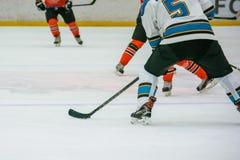Slutet lägger benen på ryggen upp av hockeyspelare på is royaltyfria bilder