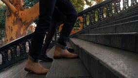 Slutet lägger benen på ryggen upp av mannen och kvinnan som går upp på trappan Foten av oigenkännligt barn kopplar ihop gammal re arkivfilmer