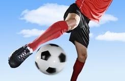 Slutet lägger benen på ryggen upp och fotbollskon av fotbollsspelaren i handling som sparkar utomhus bollen som isoleras på blå h arkivbild