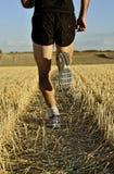 Slutet lägger benen på ryggen upp, och skor av sportmannen som kör baksida för det arga landet, beskådar perspektiv Arkivbilder