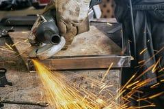 Slutet maler upp en metallprodukt med vinkelmolar arkivfoton