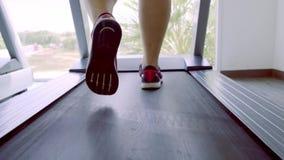 Slutet mans upp ben i rosa gymnastikskor på a Treadmill i idrottshallen stock video