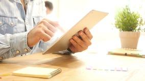 slutet räcker upp multitaskingmannen som använder minnestavlan på arbetsskrivbordet stock video