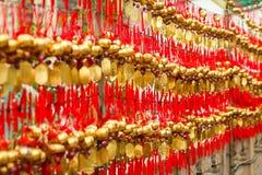 Slutet ror upp fantaster som hänger guld- bönklockor för att välsigna på på Wong Tai Sin Temple, Hong Kong arkivbilder