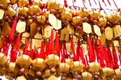 Slutet ror upp fantaster som hänger guld- bönklockor för att välsigna på på Wong Tai Sin Temple, Hong Kong royaltyfri bild