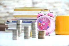 Slutet sköt klockan och staplade upp den selektiva fokusen för mynt på klockan Arkivfoton