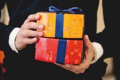 Slutet sköt upp av affärsmanhänder som rymmer ljusa gåvaaskar slågna in med strumpebandsorden Jul nytt år, födelsedag, valentin d royaltyfria foton