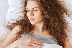 Slutet sköt upp av angenämt se kvinnligt ta sig en tupplur i bekväm säng fotografering för bildbyråer
