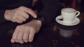 Slutet sköt upp av en hand för ` s för ung man, som kontrollerar inkommande post på den smarta klockan stock video