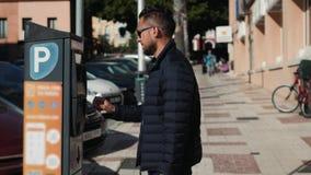 Slutet sköt upp av en man som sätter in en parkeringsplatsbiljett på en automatiserad lönmaskin Har automatiserade maskiner för k stock video