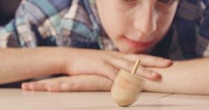 Slutet sköt upp av en pojke som rotera en Chanukkahdreidel på golvet