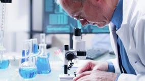 Slutet sköt upp av forskare i hans 60-tal som ser i ett mikroskop arkivfilmer