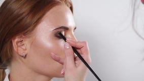 Slutet sköt upp av framsidan för kvinna` s, sminkkonstnär sätter en skugga av ögonskugga på framsida stock video