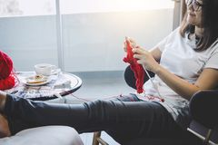 Slutet sköt upp av händer för den unga kvinnan som hemma sticker en röd halsdukhemslöjd i vardagsrummet på terrass royaltyfri fotografi