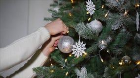 Slutet sköt upp av händer för kvinna` ett s, som dekorerar med festliga bollar en julgran i henne hem arkivfilmer