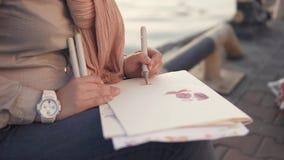Slutet sköt upp av händer för kvinna` ett s, som drar nära havet, håll för en dam en penna lager videofilmer