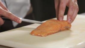 Slutet sköt upp av händerna för kock` s, mansnitt per stycke av forellen i halva stock video