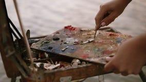 Slutet sköt upp av händerna för kvinna` s, som blandar av olje- målarfärger eller tunt smörlager med en palettkniv, färgerna är p stock video