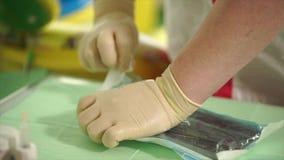 Slutet sköt upp av handen för sjuksköterska` s, som drar ut tand- instrument, polikliniken lager videofilmer