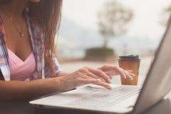 Slutet sköt upp av kvinnliga händer som skriver på ett bärbar datortangentbord Ung kvinna som studerar och arbetar i parkera Arkivbilder